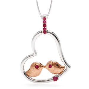 จี้นกคู่เกาะในโครงรูปหัวใจ โดดเด่นด้วยเทคนิคพิเศษชุบพิ้งค์โกลด์ (Pink Gold) ที่ตัวนก ประดับทับทิมแท้ ตัวเรือนรูปหัวใจ เงินแท้ชุบทองคำขาว